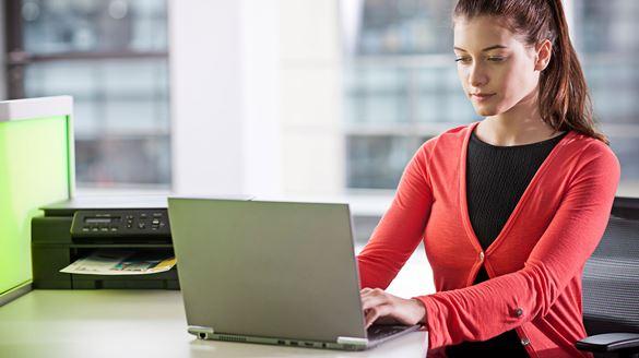 Dame jobber på en laptop på kontoret med en Brother skriver i bakgrunnen