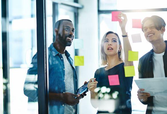 Három irodai alkalmazott ragaszt post-it jegyzeteket egy üvegfalra egy kreatív együttműködés pillanatában, üzleti találkozó során