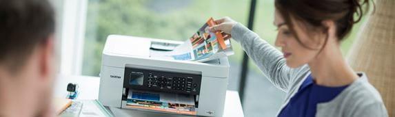 Žena sedící u stolu odebírá dokument z tiskárny