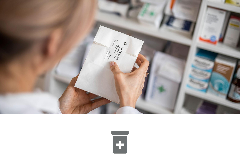 Női gyógyszerzész gyógyszert címkéz egy gyógyszertárban