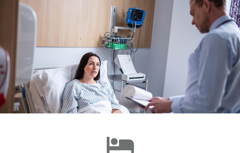 Női beteg kórházi ágyon, férfi orvos nézi a beteg kartonját, szürke ágy ikon