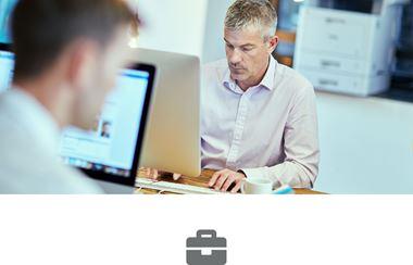 Dwaj mężczyźni siedzą przy biurkach, pracują na komputerach, drukarka laserowa w tle