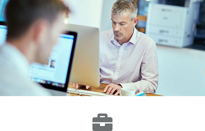 Dva moška sedita za delovno mizo z računalniki, v ozadju laserski tiskalnik