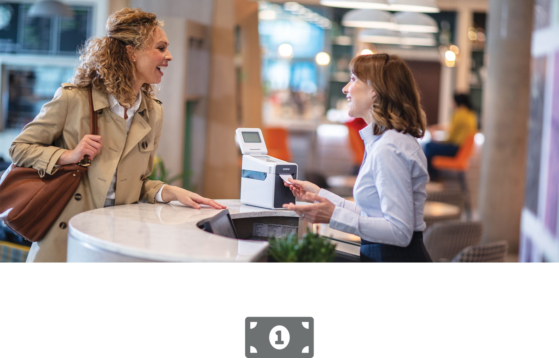Nő kiszolgál egy női ügyfelet a pénztárnál