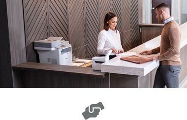 Pomoč stranki na oddelku storitev za stranke, na pultu laserski tiskalnik in tiskalnik nalepk