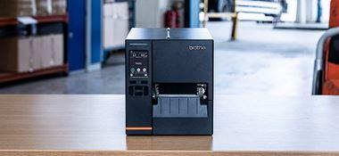 Black industrial label printer sat on table in warehouse
