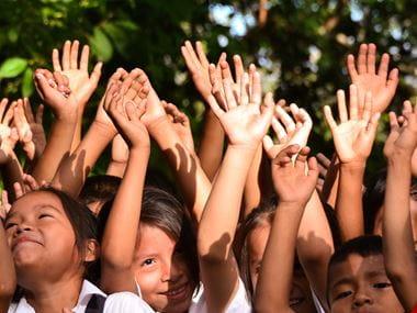 Ruce skupiny šťastně se smějících školáků