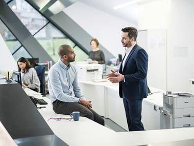 To menn i et kontormiljø som prater sammen ved en kontorpult