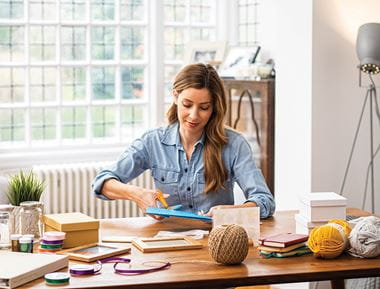 Ženska v modri bluzi sedi za domačo pisalno mizo, polno škatlic, in izdeluje ročne izdelke
