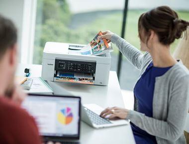 kobieta siedzi przy biurku w domu, obok ma drukarkę