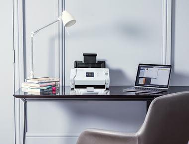 Brother skener na drvenom uredskom stolu s bijelom lampom i laptopom