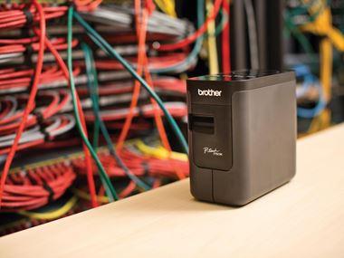 Tiskalnik nalepk PT-P750TDI na mizi pred omrežnimi kabli