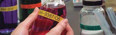 Fľaše naplnené chemikáliami na ktorých je nalepený štítok Brother P-touch TZe