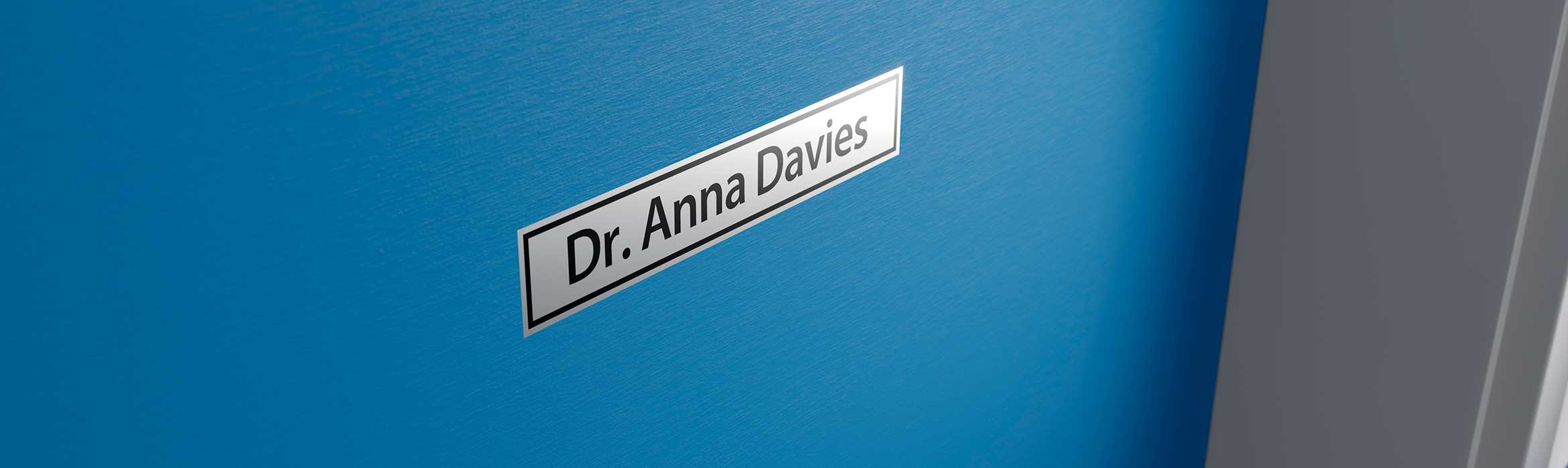 Brother black on silver label printed with name of doctor, and stuck on their door