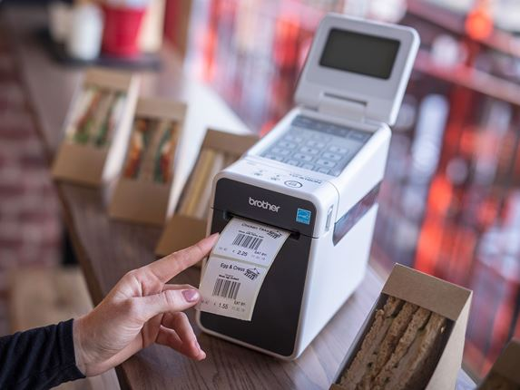 Brother TD-2000 desktop label printer with barcode label being printed