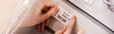 Shelf-edge label printed on Brother label printer being applied to edge of shelf