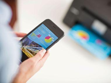 En person printer ut et dokument med iPrint &Scan app fra sin mobil til en Brother skriver