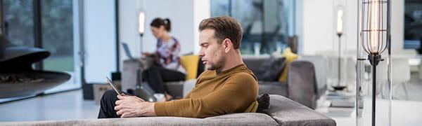 homme assis sur un canapé travaillant sur une tablette