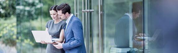 Muškarac u plavom odjelu i žena u sivoj haljini s laptopom ispred zgrade, staklena vrata, pisač unutar zgrade, drveće u pozadini