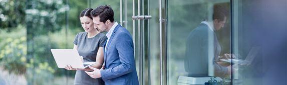 Mężczyzna o ciemnych włosach ubrany w białą koszulę i niebieski garnitur stoi i rozmawia z kobietą w szarej sukience trzymającą laptopa, szklane drzwi, drukarka w środku, zielone krzewy