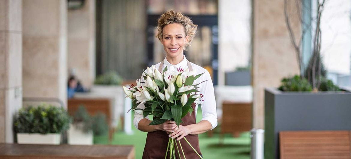 Florist holding bunch of lillies, plants, table, outdoor chairs