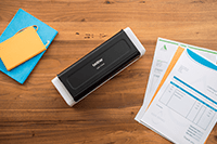ADS-1700W compact document scanner  on a desk with A4 paper