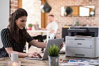 Temnolasa ženska sedi za mizo s tiskalnikom in prenosim računalnikom