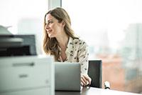 Žena sedící u stolu s notebookem a tiskárnou na stole