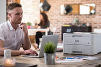 Muž sedí u stolu s multifunkční tiskárnou na stole