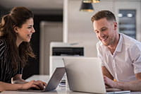 Muž a žena sedící u stolu s tiskárnou v pozadí mezi nimi