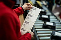 Wysokiej jakości zadrukowane etykiety trzymane przez pracownika nad linią montażową