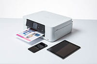 White inkjet printer surrounded by mobile devices