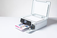 White inkjet printer with colourful output and copy/fax lid open