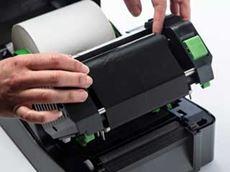 En person plasserer en etikettrull i en etikettskriver i TD4T-serien