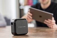 Moški s tablico in P-touch Cube Plus, ki ima baterijo
