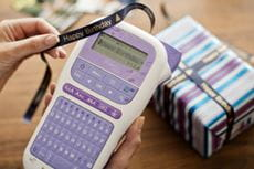 """Someone using a P-touch handheld label printer to print """"Happy Birthday"""" in gold lettering onto a black ribbon to tie around a wrapped gift"""