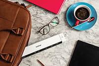 Přenosný dokumentový skener Brother DS-640, brýle, káva, kožená taška na notebook, tužka, tablet, růžový notebook
