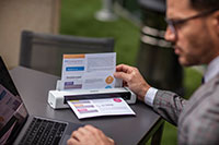Férfi szürke öltönyben, szemüveggel, laptop előtt ül és Brother DSmobile DS740D hordozható dokumentumolvasóval szkennel, színes A4-es dokumentumot
