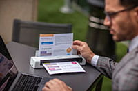 Man wearing grey suite with glasses, sat outdoors using laptop and Brother DSmobile DS740D portable document scanner with colour A4 document