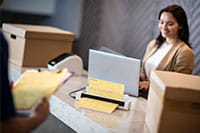 Žena sa smeđom kosom na recepciji s laptopom koristi mobilni skener dokumenata Brother DSmobile DS740D, kutije, dostavljač, mapa s kopčom