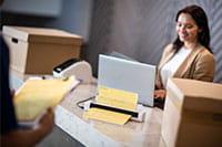 Žena s hnědými vlasy na recepci skenuje pomocí přenosného skeneru dokumentů Brother DS740D