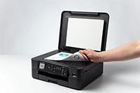 Et dokument skannes fra glassplaten på en Brother DCPJ1050DW multifunksjon farge blekkskriver