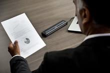 En mann på et kontor holder et utskrevet dokument som er skrevet ut på en Brother mobil skriver i PJ700-serien