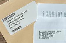 Cięta etykieta DK obok etykiety z taśmy ciągłej DK wydrukowane na drukarce Brother i przyklejone do kopert