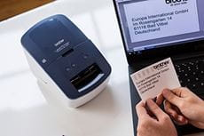 Printed address label with company logo being held in front of Brother QL-600B label printer