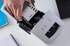 Woman loading a Brother continuous DK label roll into the Brother QL-600R label printer