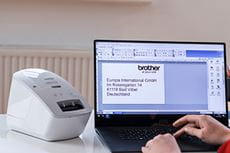 Brother QL-600R label printer next to a laptop with Brother P-touch Editor label design software on the screen, and label created ready for printing.