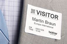Brother DK-11234 visitor badge label attached directly to grey suit jacket