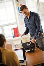 En mann på et kontor skanner et dokument på en Brother ADS2800W skanner