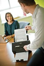 En mann skanner et dokument på en Brother ADS3000N dokumentskanner, en kvinne sitter å jobber  i bakgrunnen